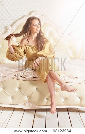 Beautiful young woman in golden dress sitting on vintage bad