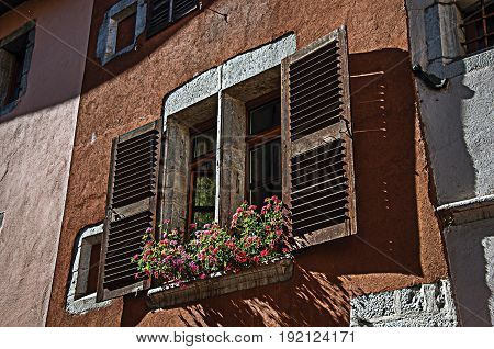 Window and flowers in an old building at the historical city center of Annecy. Located in the department of Haute-Savoie, Auvergne-Rhône-Alpes region, in south-eastern France. Retouched photo