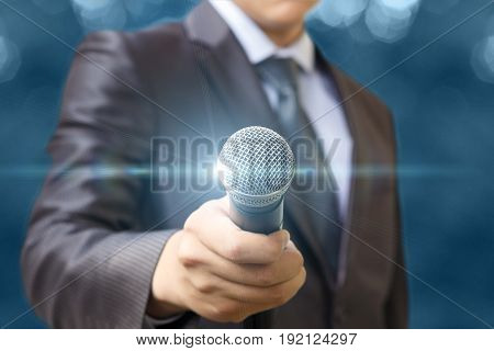 The Man Holds Out A Microphone .