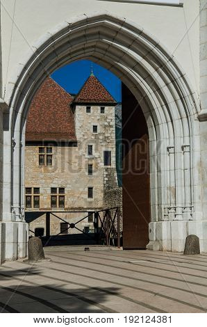 Partial view of Annecy castle through the entrance gate, stone arch in the foreground, city center of Annecy. Department of Haute-Savoie, Auvergne-Rhône-Alpes region, in south-eastern France