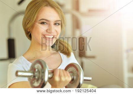 Sporty young woman training in gym lifting dumbbell