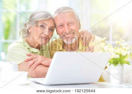 Happy senior couple sitting at table and looking at laptop