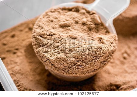 Whey protein powder for fitness nutrition to start training on wooden background