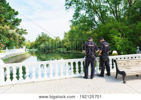 Two Police Officers Follow The Rule Of Law Around The Pond In The Dendrological Park