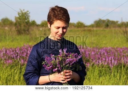 Portrait Of A Girl With Short Hair With A Bouquet Of Flowers. Looks Down And Smiles
