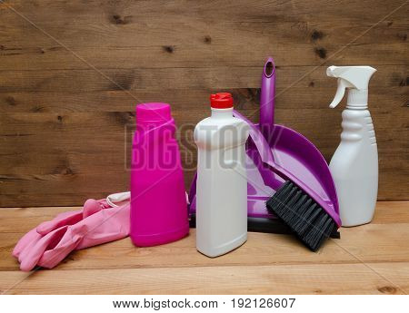 Set of variety cleaning supplies on wooden table