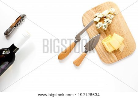 Bottle of red wine with cheese aperitive on white background space for text.