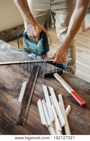 Men's hands with electric jig saws in the hand in the process of sawing wooden pieces. The concept of handmade.