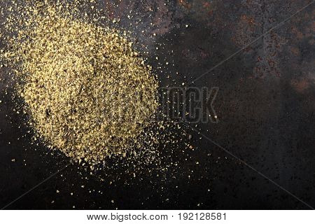 Black pepper powder on a dark rusty background with copy space