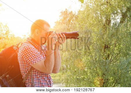 Photographer with SLR camera and backpack in nature side view