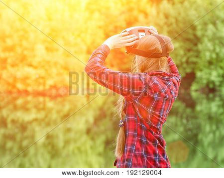 Girl shoots virtual reality glasses sunset in nature view from the back