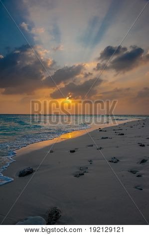 Sunset in the Maldives. Beautiful colorful sunset over the ocean in the Maldives seen from the beach.Amazing sunset and beach in Maldives. Calm water