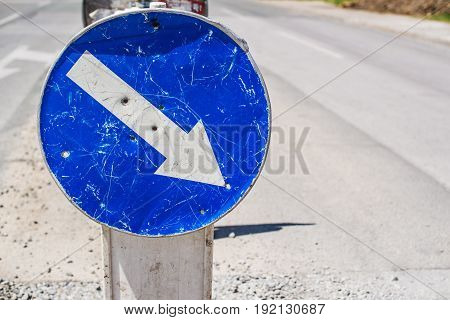 Weathered mandatory traffic direction sign on the street