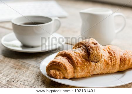 Business breakfast in office with cup of coffee, milk and croissant on wooden table background