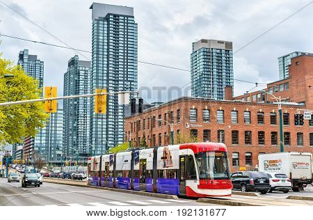 Toronto, Canada - May 2, 2017: Modern streetcar on a street of Toronto. The Toronto streetcar system is the largest and the busiest light-rail system in North America