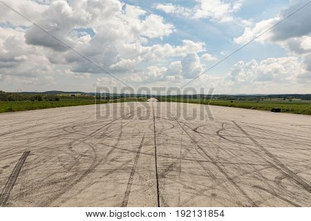 Old runway tarmac road on a sunny day. Road tire with smudges from tires. Sunny cloudy day.