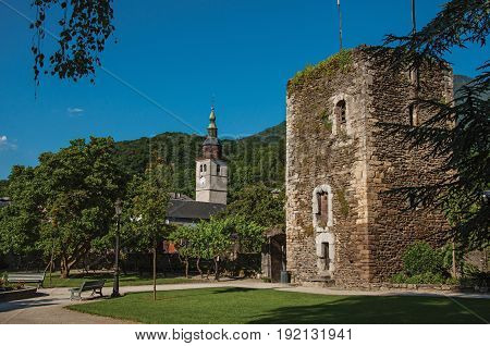 Conflans, France - June 29, 2016. Square, belfry, stone building and garden in city center of Conflans, a medieval hamlet in Haute-Savoie department, Auvergne-Rhône-Alpes region, south-eastern France