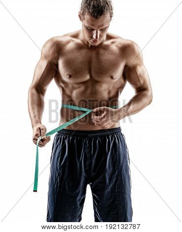 Bodybuilder with tape measures the size of the waist. Photo of young man shirtless on white background. Strength and motivation