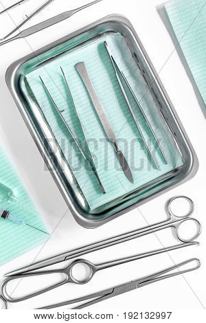 surgical instruments and tools including scalpels, forceps and tweezers on white table top view.