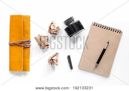 Writer workplace with vintage notebook on white background top view.