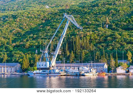 The Old Military Crane Unloads Cargo In A Small Port. Montenegro, Boka-kotor Bay.