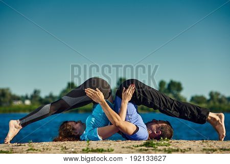 Two athletic people doing acro yoga outdoors