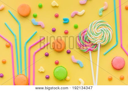 Sweets for birthday including lollipop and drops on yellow background top view.