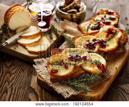 Grilled sandwich  with smoked sheep cheese, thyme  and wild red huckleberry jam on a wooden rustic table