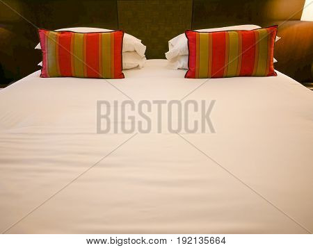 Red Pillows and White Pillows on White and Comfort Bed with Light from Bedside Lamp.