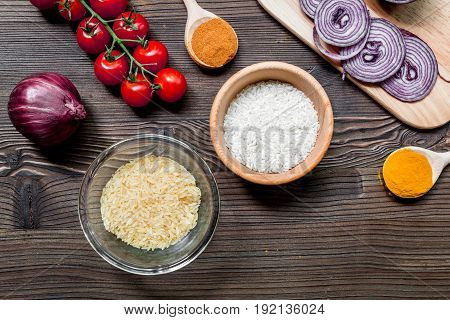 homemade paella ingredients composition with rice, tomato, onion on wooden kitchen table background top view