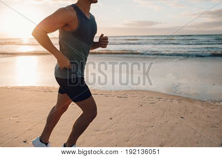 Cropped shot of fit young male runner working out on the sea shore. Young man running along the beach in morning.