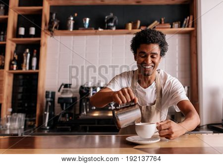 Professional barista making coffee on counter at cafe. Young african man pouring milk into cop and smiling.