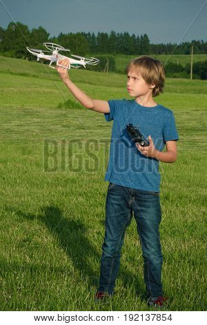 Boy playing with the drone and remote control outdoors.