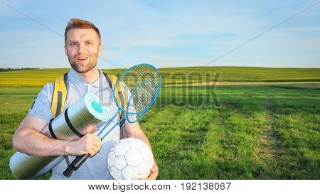 A cheerful young man on picnic with backpack, rackets for badbotton and ball smiles on background of green meadow. Camping, actively spending time outdoors