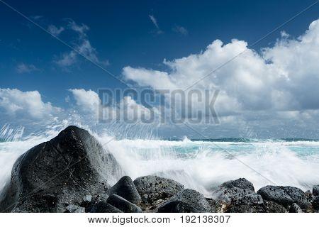 Cresting ocean waves crash against rocks of coastline showing trails of water in the surf