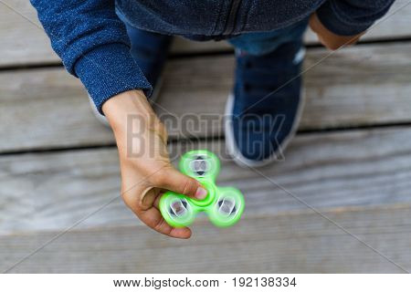 Boy playing with popular fidget spinner toy. Top view