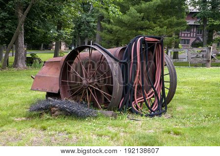 An antique water wagon with hoses sits on the lawn