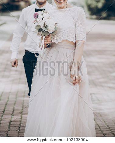 Stylish Wedding Bride And Groom Walking In Sunny Park. Modern Couple Holding Fashionable Bouquet, Wo