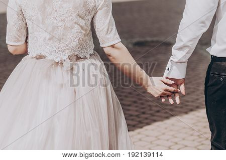 Stylish Wedding Bride And Groom Walkingn In Sunny Park, Happy Moment. Modern Couple Holding Hands Cl