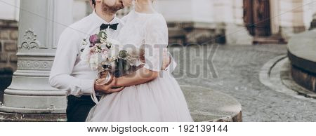 Stylish Wedding Couple With Bouquet. Modern Bride And Groom Holding Fashionable Bouquet  And Hugging