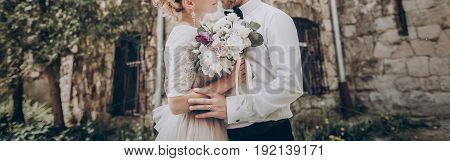 Stylish Wedding Couple With Bouquet. Modern Bride And Groom Holding Fashionable Bouquet At Old  Cast