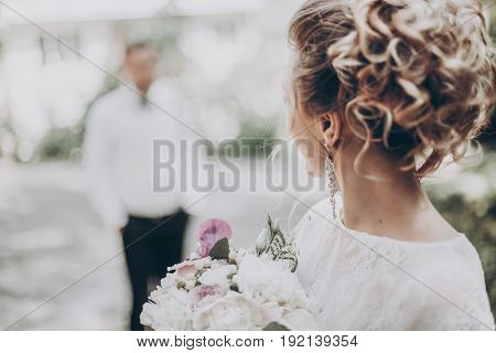 Stylish Wedding Bride With Bouquet And Amazing Modern Dress. Bride Posing And Looking At Groom In Su