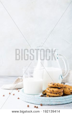 Chocolate chip cookies on blue stone plate with glass of milk on light gray background. Selective focus. Copy space.