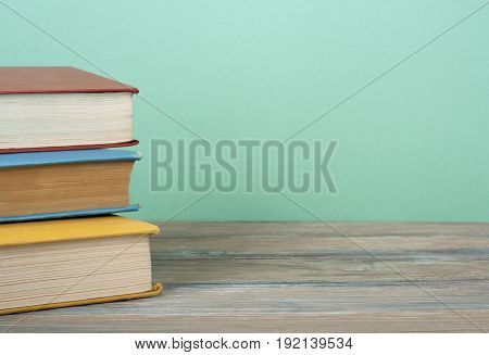 Colorful books on the table against the background of green wall