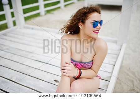 Portrait Of An Attractive Girl Posing In Bikini With Sunglasses On While Standing On A White Wooden