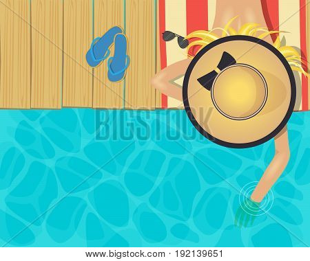 Woman lying on a pier wearing a big hat touching the water with one hand
