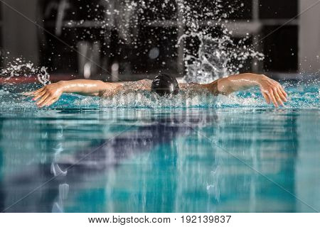 Male swimmer swimming the butterfly stroke in a pool