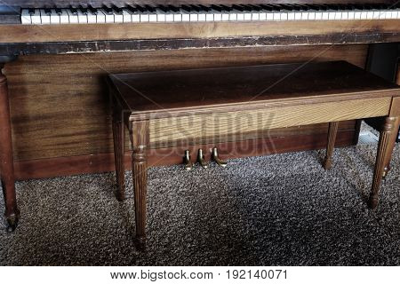 Old piano with ivory and ebony keys wooden bench