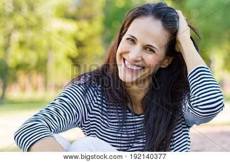Happy latin woman having fun at park while touching hair. Hispanic woman enjoying holiday while sitting on grass in park. Portrait of smiling mature woman relaxing and looking at camera.
