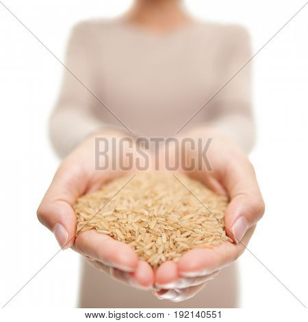 Brown rice grains natural food closeup in open hands. Woman showing uncooked raw rice grain in studio.